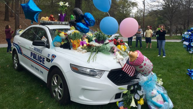 Flowers and small tributes are left on Officer Allen Jacobs' cruiser Saturday.