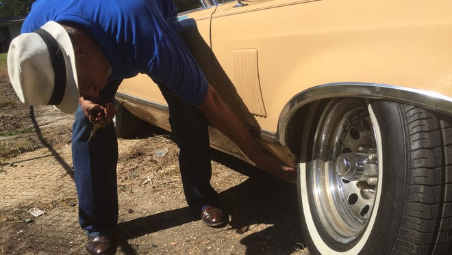 Michael Starks, a resident of the Queens neighborhood in northwest Jackson, checks out the damage to his 1978 Ford Thunderbird caused by one of Jackson's many potholes.
