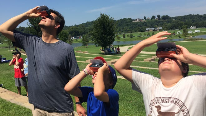 "Bryan Belanger and Shane and Joseph of Detroit Watch the eclipse at Liberty Park in Clarksville on Monday, Aug. 21. Belanger spotted a change in the sun around noon. ""A little bite is being taken out,"" he said"