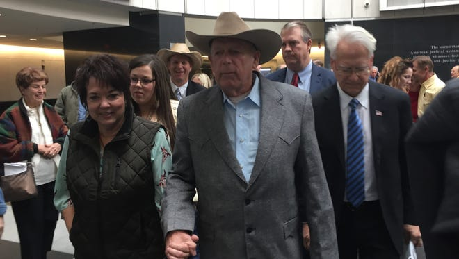 Cliven Bundy, his wife, Carol Bundy, and his lawyer Bret Whipple walk through the lobby of a Las Vegas federal courthouse on Jan. 8, 2018.