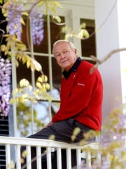Arnold Palmer sits on the clubhouse railing at the Augusta National Golf Club in Augusta, Ga. Palmer died Sunday at 87.