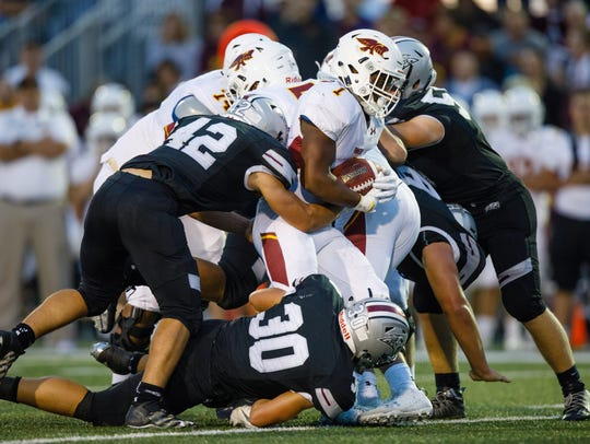 Ankeny High School's Ray Crawford (1) is stuffed at