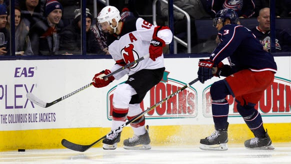 New Jersey Devils forward Travis Zajac, left, chases