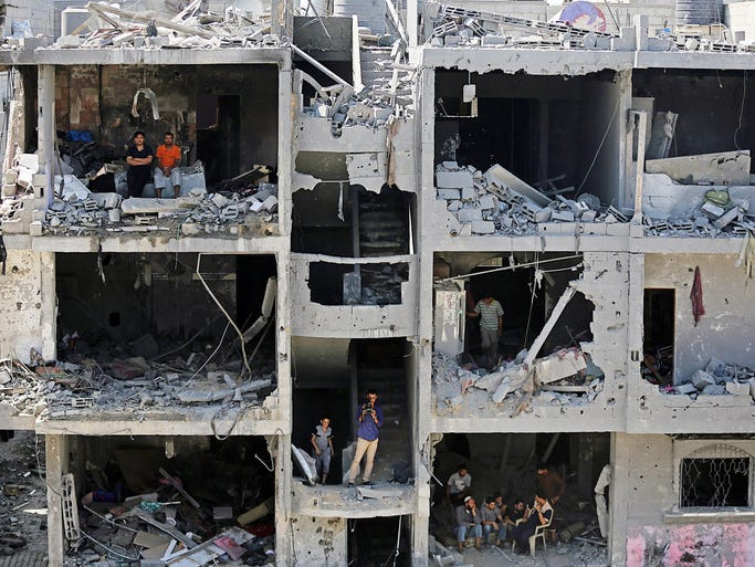 Palestinians sit on rubble of houses destroyed after Israeli airstrikes in Rafah, southern Gaza Strip.