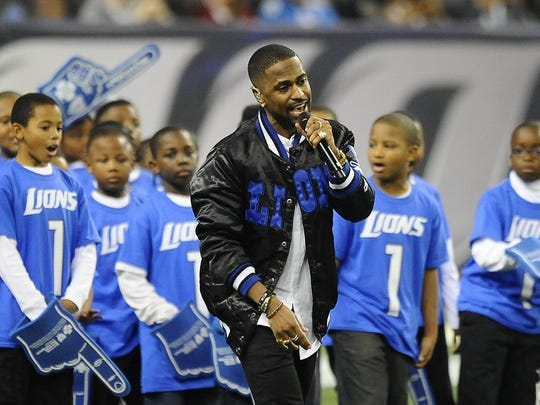 """The Detroit rapper opened the show by walking slowly from the players' tunnel onto Ford Field, performing """"One Man Can Change the World"""" while joining a few dozen children from Detroit PAL."""