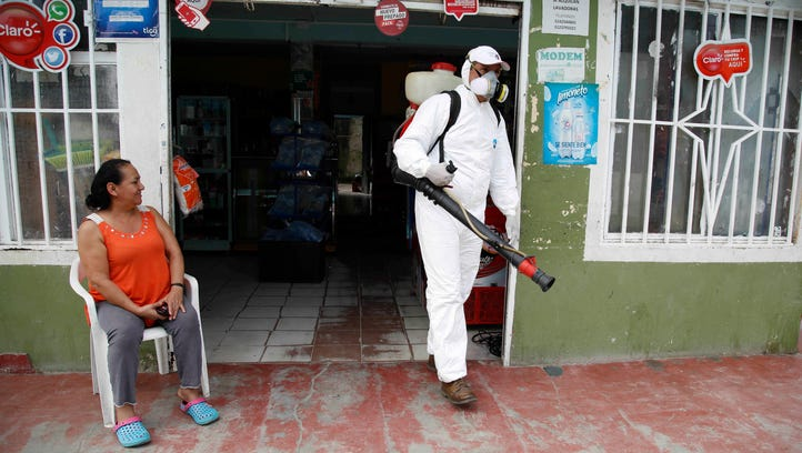 A health worker walks away from the home of Maria Cardenas, left, who was diagnosed with Zika, after he sprayed insecticide to kill mosquitoes on her property in Acacias, Colombia, on Feb. 4, 2016.