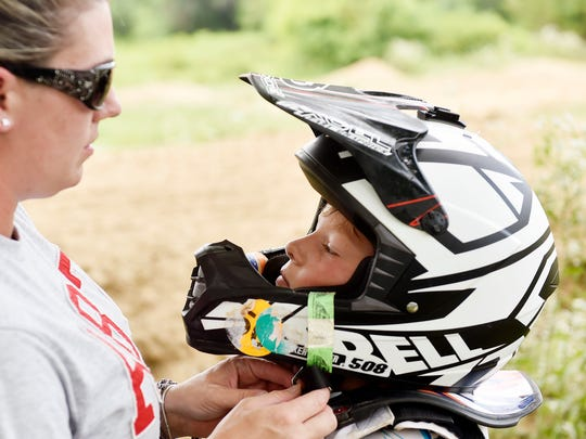 Danielle Peck helps fasten her son Parker Dwyer's helmet before he returns to riding his dirt bike Wednesday, July 13, 2017, in Fawn Township. Dwyer's mother, Danielle Peck, said Dwyer began riding dirt bikes at age 2 and racing at age 4, and has gone through five dirt bikes. His grandfather, uncle and father have all raced, and maintain a dirt track on Dwyer's grandfather's property that they alter to keep challenging Dwyer.