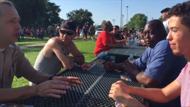 A Wichita police officer sits down with a group of Wichitans at a community barbecue Sunday.