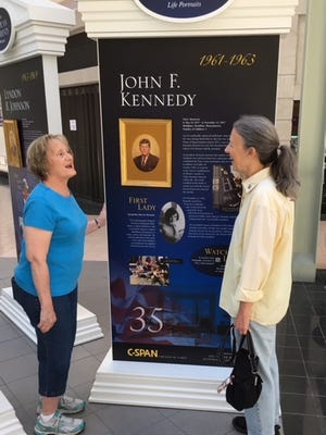 """Roberta Wallick of Red Lion, left, and Terry Garland of Mount Wolf talk about the portrait of President John F. Kennedy.  The portraits of all the Presidents of the United States are on exhibit in two clusters on the second floor of the Galleria Mall through August 16.  As Terry Garland said:  """"This is an ideal thing to bring children to see."""""""