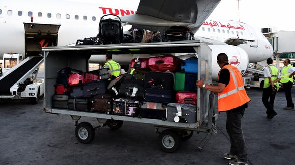 A worker pushes a luggage cart at Tunis-Carthage International