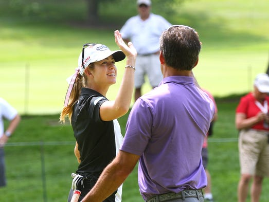 Paula Creamer gives a high-five to Wade Sakis after he sunk his putt on the 11th-hole during the pro-am.