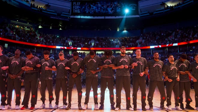 Toronto Raptors players lock arms during the singing of the national anthems before a preseason NBA basketball game against the Golden State Warriors in Vancouver, British Columbia, Saturday Oct. 1.