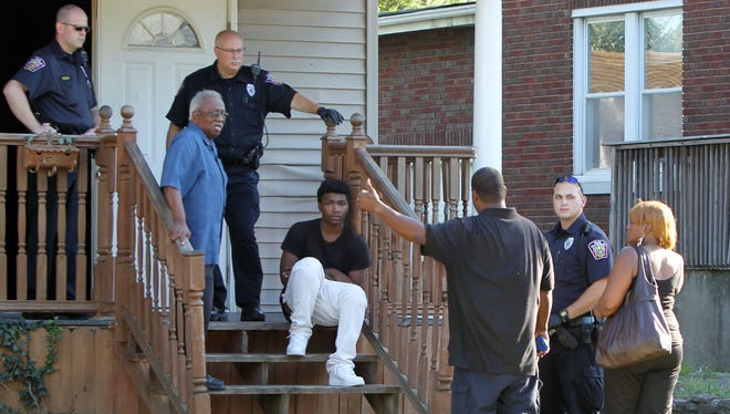 Police speak to residents of a home in the 1900 block of Goodman Avenue in North College Hill where an 11-year-old was shot Monday evening.