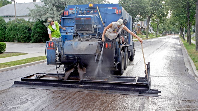 Mike Daffison, left, and Micah Jacobson of Struck and Irwin Paving, apply slurry seal Aug. 12, 2011, to East Bennett Avenue in Milwaukee's south side.