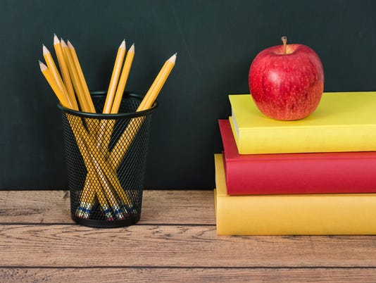 Stack of school books with apple and pencils