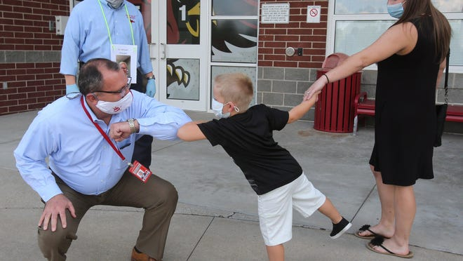 David Fischer, superintendent of the Sandy Valley Local School District, bumps elbows with Ryker Reid-Polka as the kindergartener arrives to tour Sandy Valley Elementary School during the school's open house for new families.