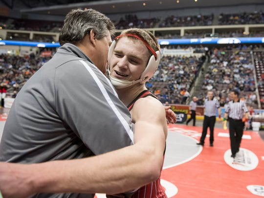 Bermudian Springs' Austin Clabaugh hugs assistant varsity coach Dan Dull after winning his semifinal bout against Quaker Valley's John Rocco Kazalas during the PIAA wrestling championship at the Giant Center in Hershey, Pa., on Friday, March 10, 2017. Clabaugh won by decision 5-0.