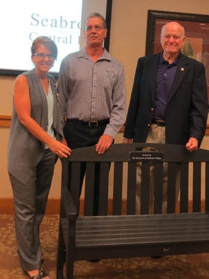 from left, Seabrook Project Manager Karen Kollmer presents Trex composite bench to Tinton Falls Director of Public Works Gary Gebele and Tinton Falls Council President Gary Baldwin.