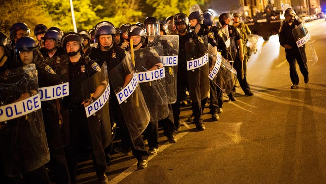 Police in riot gear line up near the scene of Monday's riots before a 10 p.m. curfew April 29 in Baltimore.