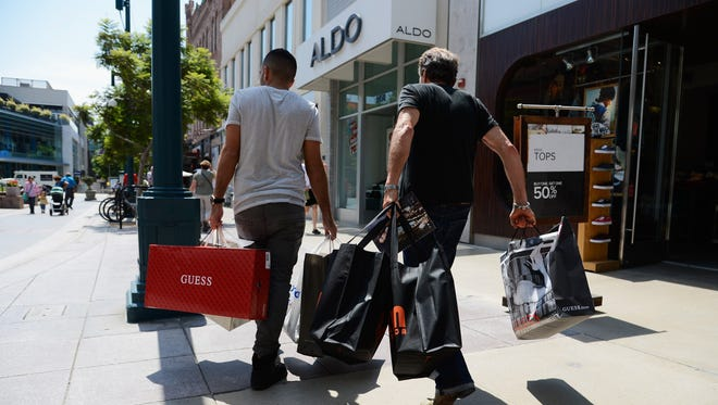 Consumers are feeling more optimistic this summer. Shoppers walk down the Third Street Promenade's outdoor shopping mall.