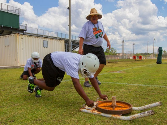 Dunbar High School's assistant football coach Phil Vogt works with his players Monday afternoon during strength and conditioning drills.