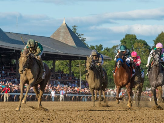 FILE- In this Aug. 24, 2019, file photo, Code of Honor, left, with jockey John Velazquez, leads the field to the finish line to win the Travers Stakes horse race at Saratoga Race Course in Saratoga Springs, N.Y. The Breeders' Cup Classic pits West Coast star McKinzie against Code of Honor, the East's top horse who finished second in the Kentucky Derby. (Skip Dickstein/The Albany Times Union via AP, File)