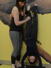 Elizabeth Pate, an instructor at Vogue Yoga, helps Bradley Wilson with a headstand while teaching a yoga class at the Children's T.R.E.E. House Museum Saturday, Feb. 28, 2015.