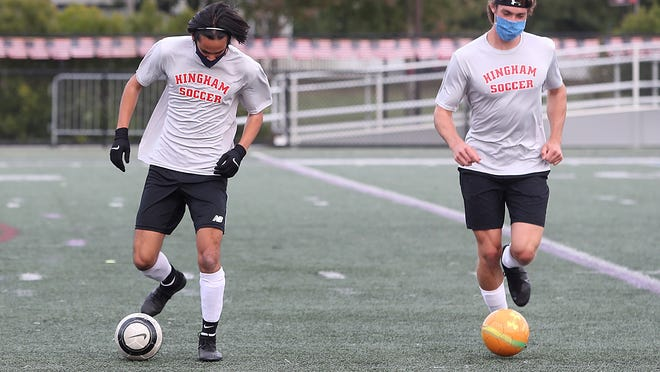 Junior Tetor Nghiem and senior Paul Forbes dribble the soccer ball up the field during a pre-season practice.