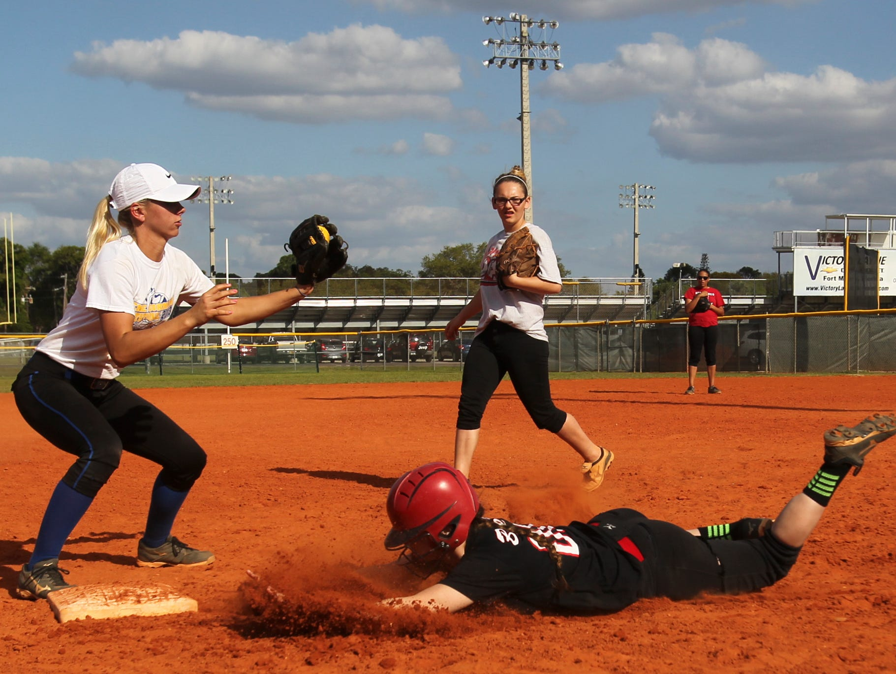 Jessie Valerius catches the ball while runner Summer Ackerson is safe after a rundown attempt during softball practice in North Fort Myers Wednesday.