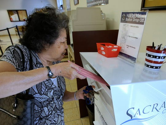 Lei Linh-Pham drops off her mail-in ballot at the Sacramento