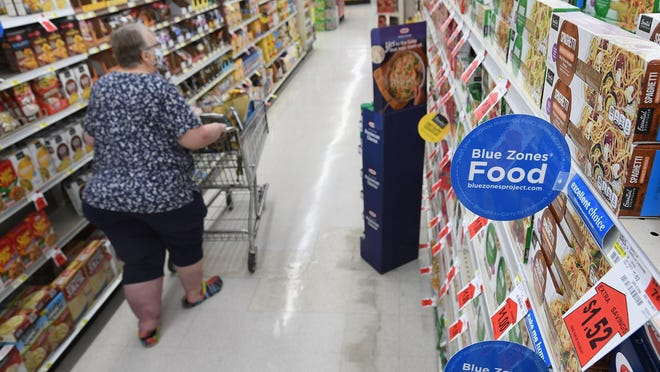 Linda Heslink, 69, of Clymer, New York, shops Monday in an aisle marked with Blue Zones signs at Sander's Market in Corry, which has been designated as a Blue Zones-approved grocery store. The market now features signage about healthier foods that are stocked in the store as well as nutritious recipes and other information.