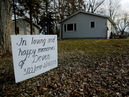 """A year after the death of Deven Guilford, a sign reads """"In Loving and Happy Memories of Deven ... 3/22/1997 - 2/28/2015"""" in front of a house by the sidewalk off Charlotte Street in Mulliken Friday, Feb. 19, 2016."""