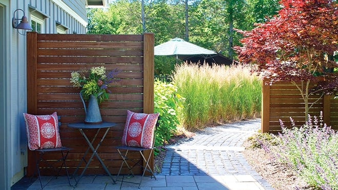 A diagonal pathway lined with feather reed grass shields the pool; privacy screens were offset to frame a Japanese maple and lead your eye down the path.