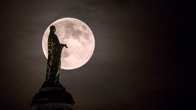 The full moon silhouettes the statue of the Virgin Mary on top the University of Notre Dame's golden dome on Monday, Sept. 8, 2014, in South Bend, Ind.