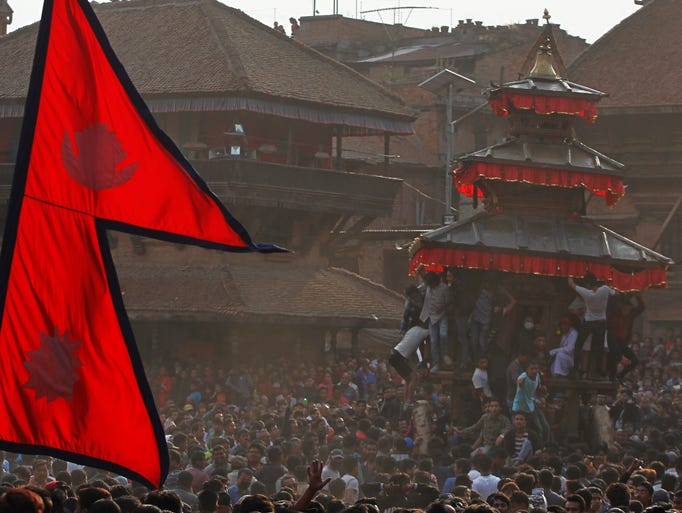 A Nepalese flag stands in the foreground, as devotees