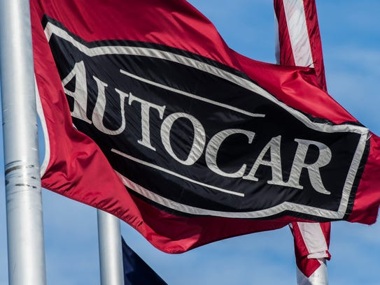 A flag hangs from a pole near the entrance to Autocar