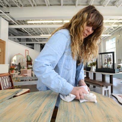 Owner Kelly Wiler buffs shelves for a curio cabinet