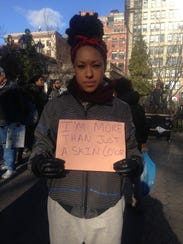 Courtney Cook, 25, of Brooklyn, holds up a sign at
