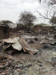 The ruins of burnt out houses stand in Baga village