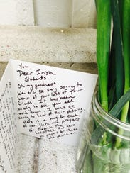 A card and flowers are placed near the location of