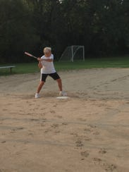 Mary Sesing prepares to hit the baseball at the game