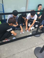 Line waiters for Apple's iPhone 6S play cards to pass