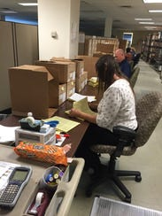 Analysts sort through boxes to research weapons sales.