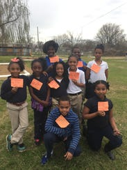 Julius Patrick Elementary students hold cards describing