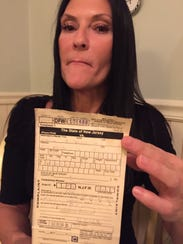 Maria Vaccarella of Howell holds the summons she received