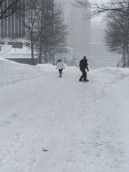 A snowboarder and pedestrian cross paths on Wilson