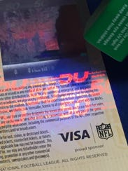 A Super Bowl 50 ticket under black light, showing the