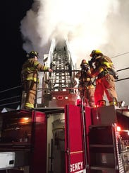 Smoke begins to cover the ladder of a fire engine on