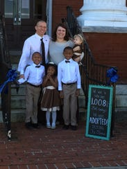 Richard and Brittany Oden stand with their children,