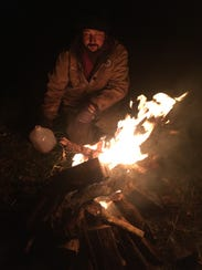 A volunteer lights a fire to protect Alstede Farms'